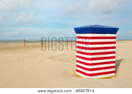 Beach of German wadden island with typical striped chair and volley ball net