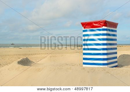 Beach of German wadden island with typical striped chair and the sea