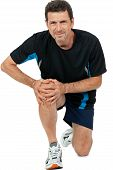 stock photo of knee-cap  - adult attractive man in sportswear knee pain injury ache isolated on white - JPG
