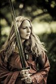 stock photo of sword  - Beautiful blond sexy woman warrior with sword outdoor