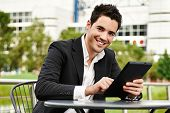 stock photo of buildings  - Young successful businessman with tablet outdoors - JPG