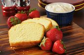 stock photo of pound cake  - Sliced pound cake fresh strawberries and whipped cream on a cutting board - JPG