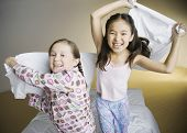 stock photo of pillow-fight  - Two girls having pillow fight - JPG