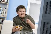 stock photo of obese children  - Smiling overweight boy eating bowl of fruit in front of television - JPG