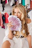 picture of bundle money  - Fashionable girl sitting with a bundle of money in a store - JPG