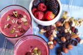 image of fruit shake  - Two glasses of berries smoothies topped with dried fruits and nuts - JPG