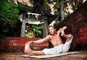 picture of dhanurasana  - Yoga akarna dhanurasana archer pose by man in white trousers near stone temple at sunset background in tropical forest - JPG
