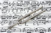 stock photo of tuning fork  - Pitchfork on sheet music abstract art background - JPG