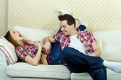 stock photo of tickling  - Playful guy tickling his girlfriend - JPG
