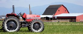 stock photo of barn house  - a serene farm setting with a barn and tractor - JPG
