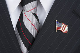 stock photo of lapel  - A politician wearing an American flag lapel pin symbolizes patriotism - JPG