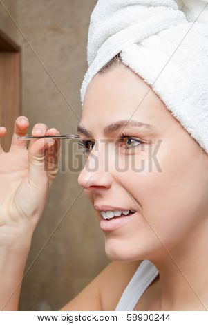 Portrait of girl plucking eyebrows with tweezers