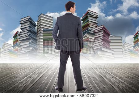 Serious businessman with hand in pocket against abstract blue design in futuristic structure