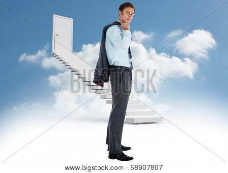Serious businessman holding his jacket against steps leading to closed door in the sky