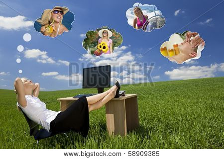 Business concept shot of a beautiful young woman relaxing at a desk in a green field day dreaming, of being on holiday. Dream clouds fill the blue sky.