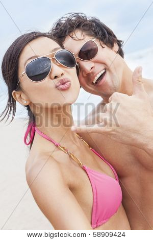 Man & woman Asian couple, boyfriend girlfriend in bikini, taking vacation selfie photograph at the beach