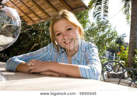 Teenage girl leaning on table outdoors