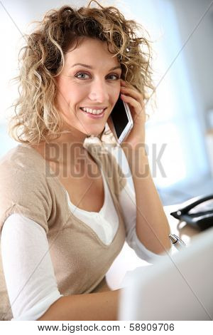 Beautiful saleswoman in office talking on the phone