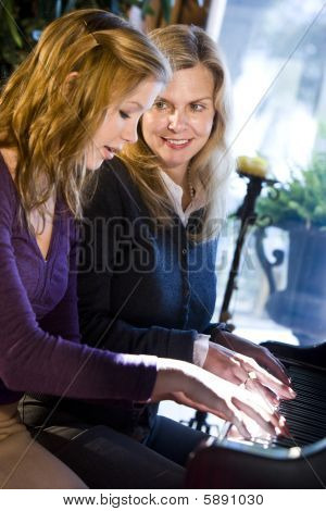Mother and daughter playing piano duet