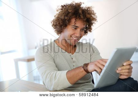 Cheerful man using digital tablet in home office