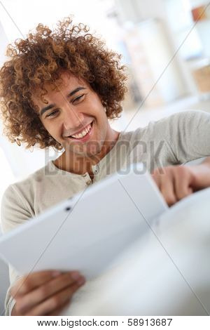 Cheerful mixed-raced guy websurfing on tablet