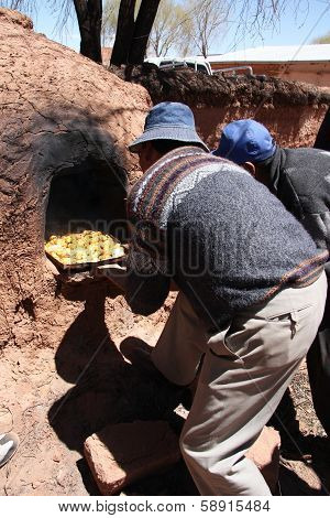 Indian men cook in Clay Oven in South America