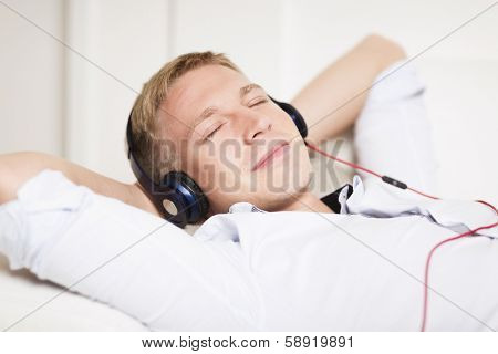 Close up portrait of young man relaxing with hands behind head and listening music at earphones while lying down on couch.