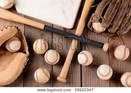 High angle shot of old and use baseball equipment on a rustic wood surface. Items include, baseballs, bats, home plate, catchers mitt and glove.