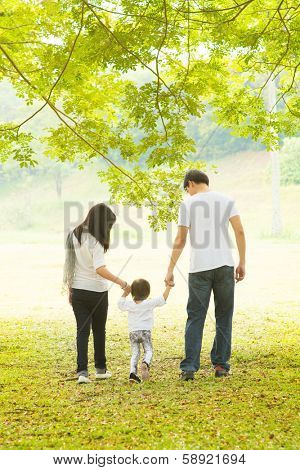 Happy Asian family outdoor activity. Rear view of parents and daughter having fun and walking on green lawn.