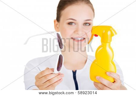 Young female doctor or nurse showing sunscreen and sun glasses fot sun uv protection. Isolated on white