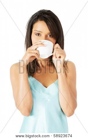 Attractive woman in nightwear drinking from cup, isoalted on white.