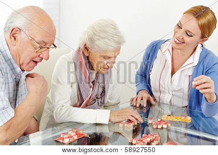 Senior couple playing Bingo with eldercare assistant in nursing home