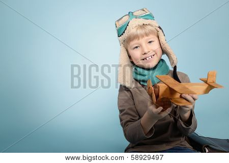 Little boy aviator dreaming and playing with wooden handmade toy plane, vintage toned