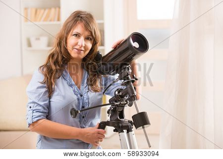 Beautiful woman looking skyward through astronomical telescope standing near a window
