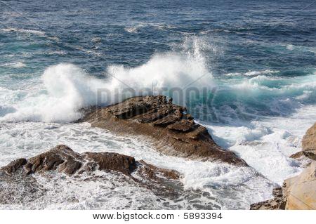 Wave Crashes Over Rocks