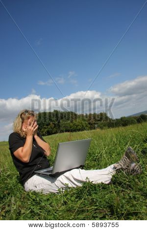 a shocked woman with a laptop sitting in the meadows