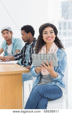 Smiling casual woman using digital tablet with group of colleagues behind in a bright office