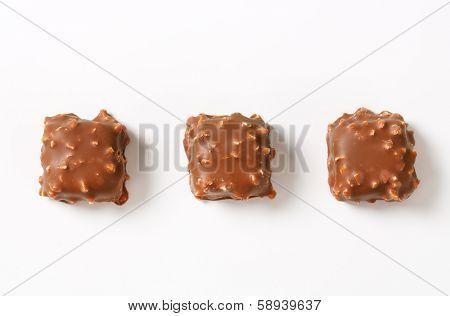 three milk chocolate pralines with nuts