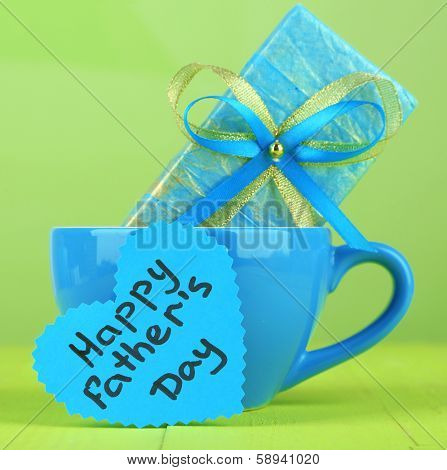 Happy Fathers Day tag with gift box and cup, on wooden table, on light background