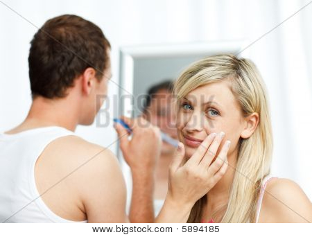 Mulher colocando o creme no rosto e limpeza dos dentes do homem