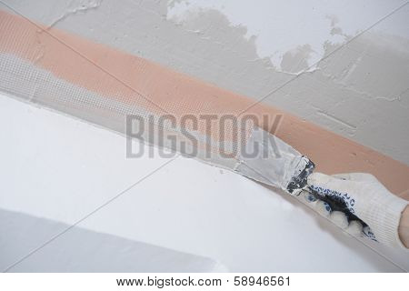 Contractor plastering a ceiling using plaster net