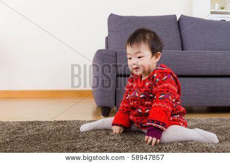 Baby girl seating on carpet
