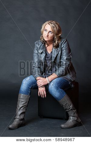 Young Blonde Woman Wearing Jeans Sitting On Cube