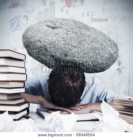 Man at office with stone overhead overworked
