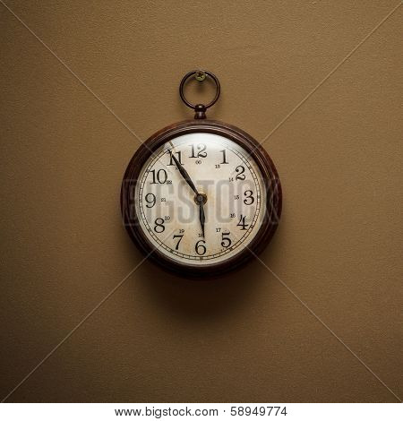 Retro vintage clock on simple brown wall background