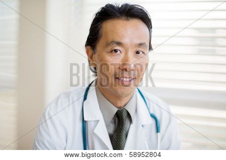 Portrait of Asian male cancer specialist with smiling in hospital