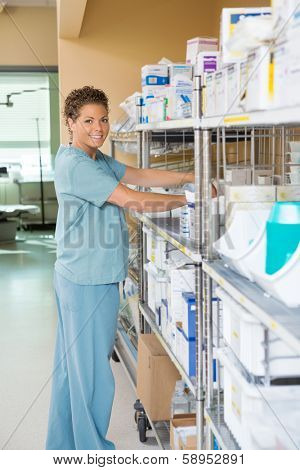 Side view portrait of female nurse smiling while working in storage room of hospital