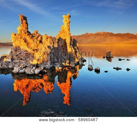 Outliers - calcareous tufa formation on the smooth water of the lake. Orange sunset. The magic of Mono Lake.