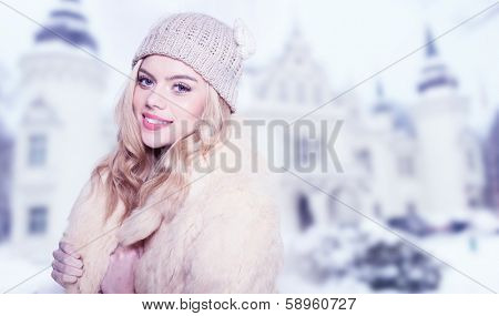 Beautiful stylish young woman with a lovely friendly smile and long blond hair in winter fashion wearing a woollen cap, scarf and jersey over a blurred background of a historical building