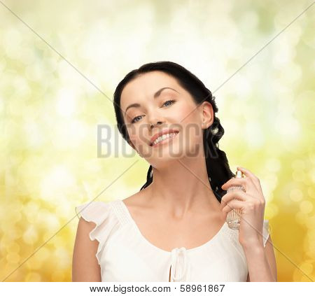 cosmetics and beauty concept - beautiful woman spraying pefrume on her neck
